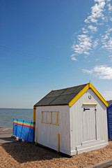 White and yellow English beach hut by seaside