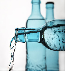sparkling water pouring from blue bottle