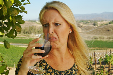 Beautiful woman cringes as she is wine tasting at a winery.