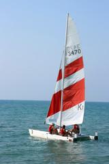 Yacht with sportsmen in the dark blue sea