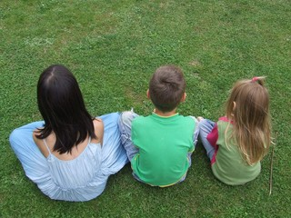 Drei sitzen im Gras