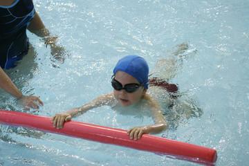 petit garçon qui apprend à nager dans une piscine