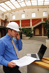 contractor in hardhat calling by phone and work with laptop