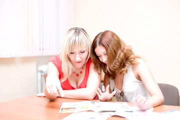 Two beautiful girls are looking through a magazine