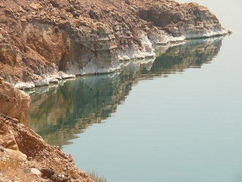 Dead Sea rocky salty coastline, unruffled sea water surface