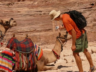 Male tourist taking picture of lying camel, Petra, Jordan