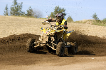Teenager on a yellow quad bike sliding