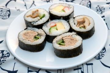 sushi rolls on round plate on white kimono background
