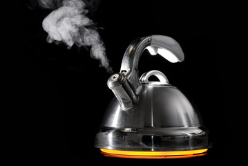 Tea kettle with boiling water on black background