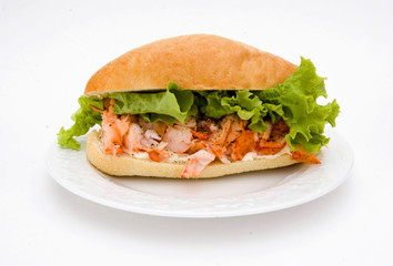 A delicious lobster sandwich with lettuce and a bun.