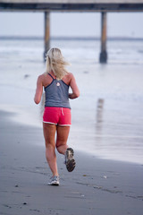 Sexy blond woman in red short jogging along the beach 2