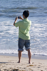 Asian man taking a picture at the beach