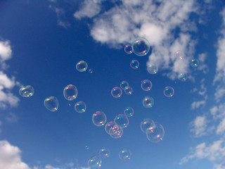 Colorful Soap Bubbles Against Blue Sky Background