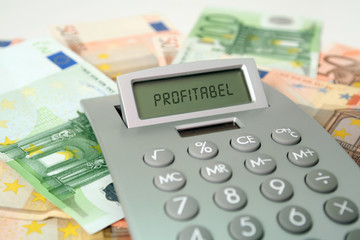 Taschenrechner und Umsatz, mit großer Menge Bargeld