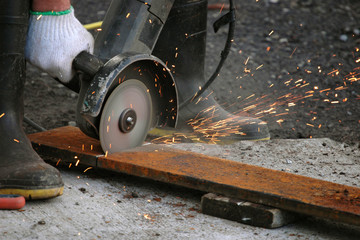 Factory worker cutting metal