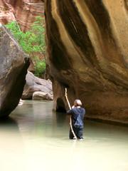 hiker walking in water of virgin river in zion national park