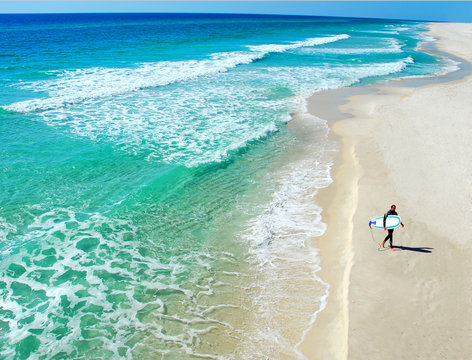 Lone Surfer on Beautiful Deserted Beach