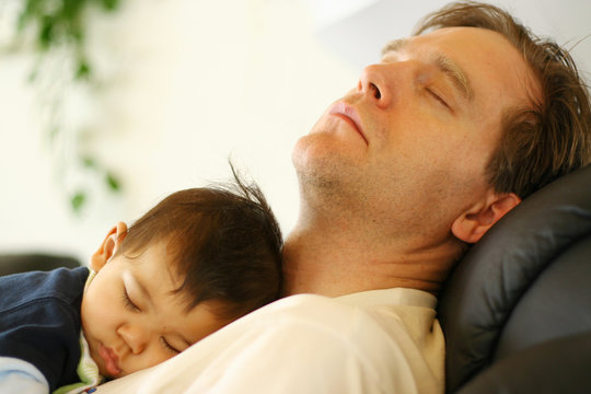 Adorable and sweet little baby sleeping on Dad's chest