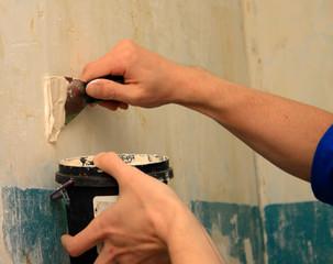 human arm repairs a wall