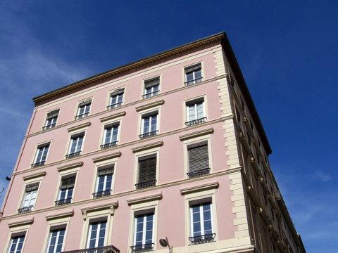 Immeuble rose et crème, Ciel bleu. Lyon. France.