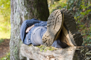 Hiker lying on a wooden bench