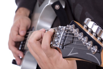 Electric guitar close up showing fingers playing it