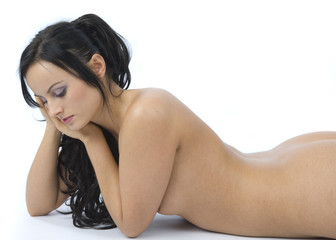 Beautiful nude brunette lying on white floor