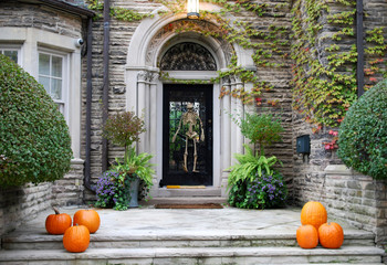 House entrance with skeleton and pumpkin Halloween decorations