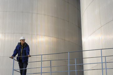 engineer in front of oil tanks