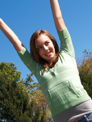 teenage girl with arms in air with blue sky
