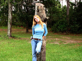 lovely girl leaning on tree in her yard