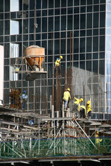 building construction site with cement bucket  and workers