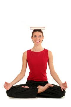 Woman in yoga pose balancing book on head