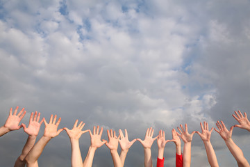raised hands on cloudy sky background