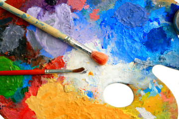 Two Brushes lay on an art palette in bright paints