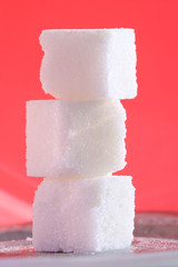 Close-up of three sugar cubes at the pink background