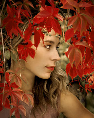 The beautiful blonde in red leaves of grapes