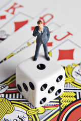Business figurine, dice, and playing cards