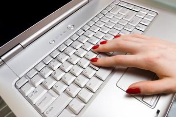 Woman fingers on laptop keyboard