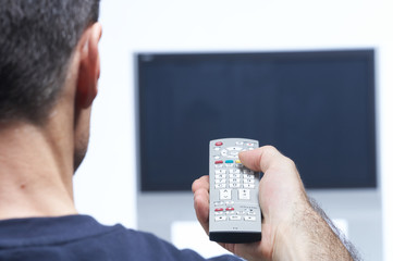 Man with remote control and flat tv