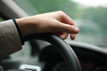 Driver's hand on steering wheel.