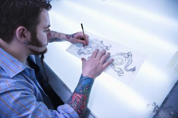 Man designing tattoo.