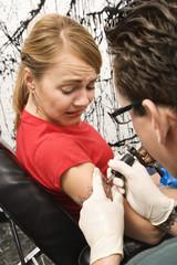Woman getting tattooed.