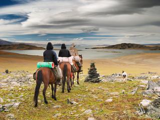 Horseriders in mongolian wildernesss