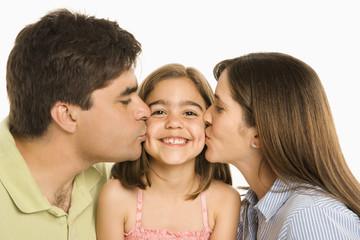 Parents kissing daughter.
