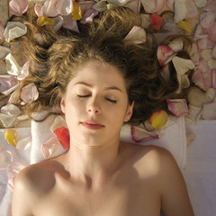 Woman lying down with hair spread out on rose petals.
