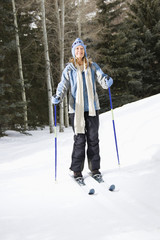 Female skier wearing blue ski clothing standing on ski slope.