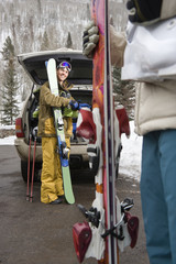 Couple standing with ski equipment by open vehicle smiling.