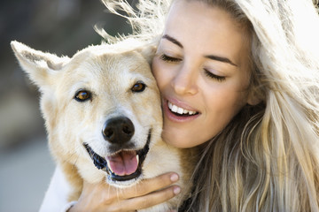 Blond woman hugging brown dog and smiling.