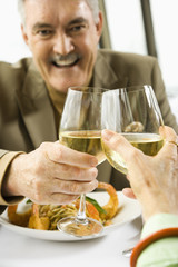 Caucasian mature couple toasting with white wine.